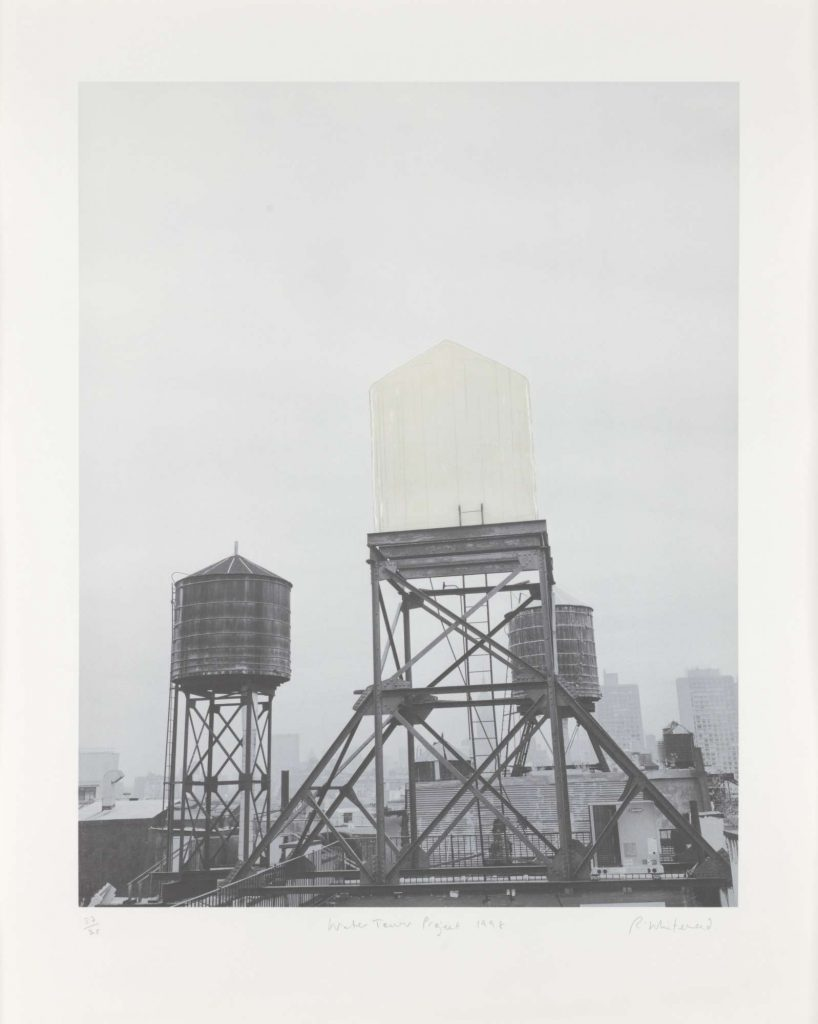 A black-and-white photograph of rooftops showing a ghostly white water tower among two other regular ones