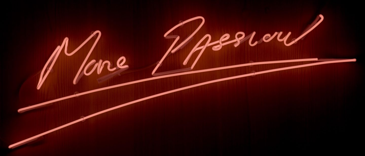 A bright pink neon spells out the words