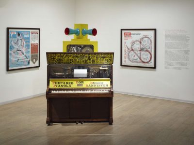 The pianola installed in an exhibition with the two related prints hung on the walls behind it