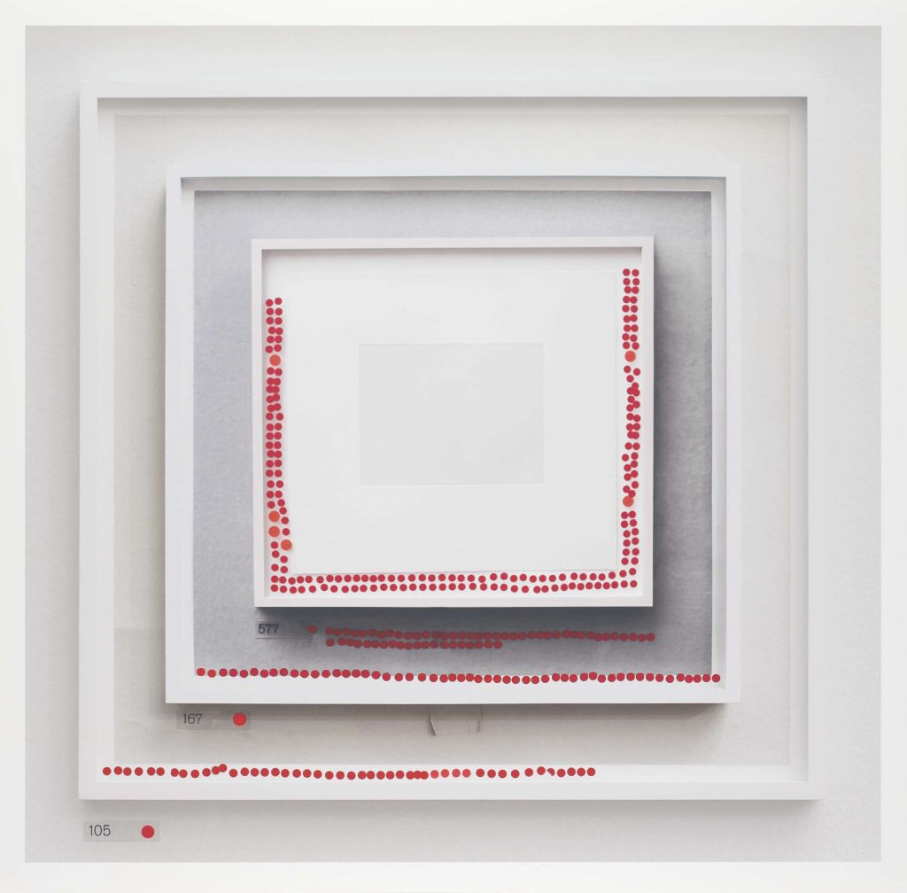 A framed photograph showing a framed photograph of a blank page within a framed photograph, within a framed photograph. Each frame has a series of red dot stickers around the edge.