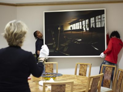 Two art handlers hang a picture on a wall under the direction of a curator