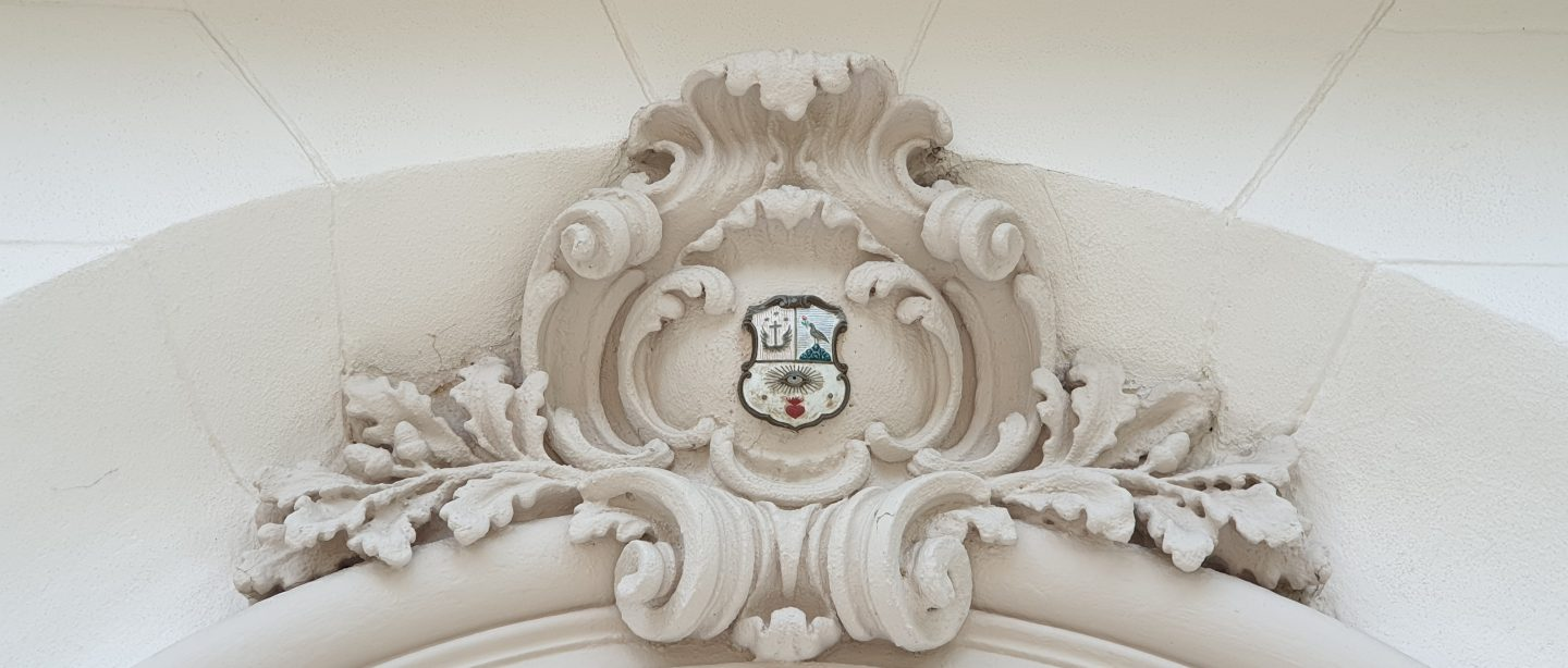 a family crest on a lintel on the exterior of the British Residence in Budapest