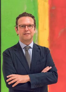 Photograph of Alex Faequharson who is standing in front of a brightly coloured artwork