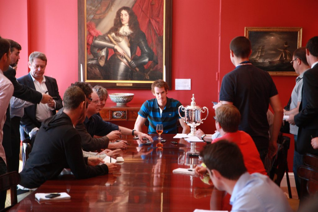 Tennis player Andy Murray seated with his US Open trophy in the dining room of the Consul General in New York surrounded by people. The GAC's painting of the Duke of York hangs on the wall behind him.