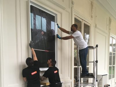 Three art technicians installing a picture on to a wall at the Ambassador's Residence in Paris