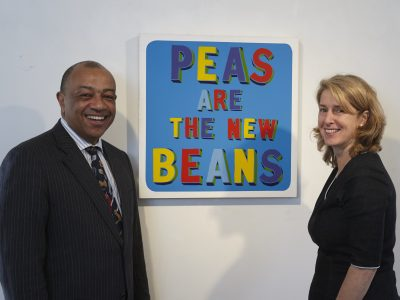 Man and woman standing in front colourful text painting