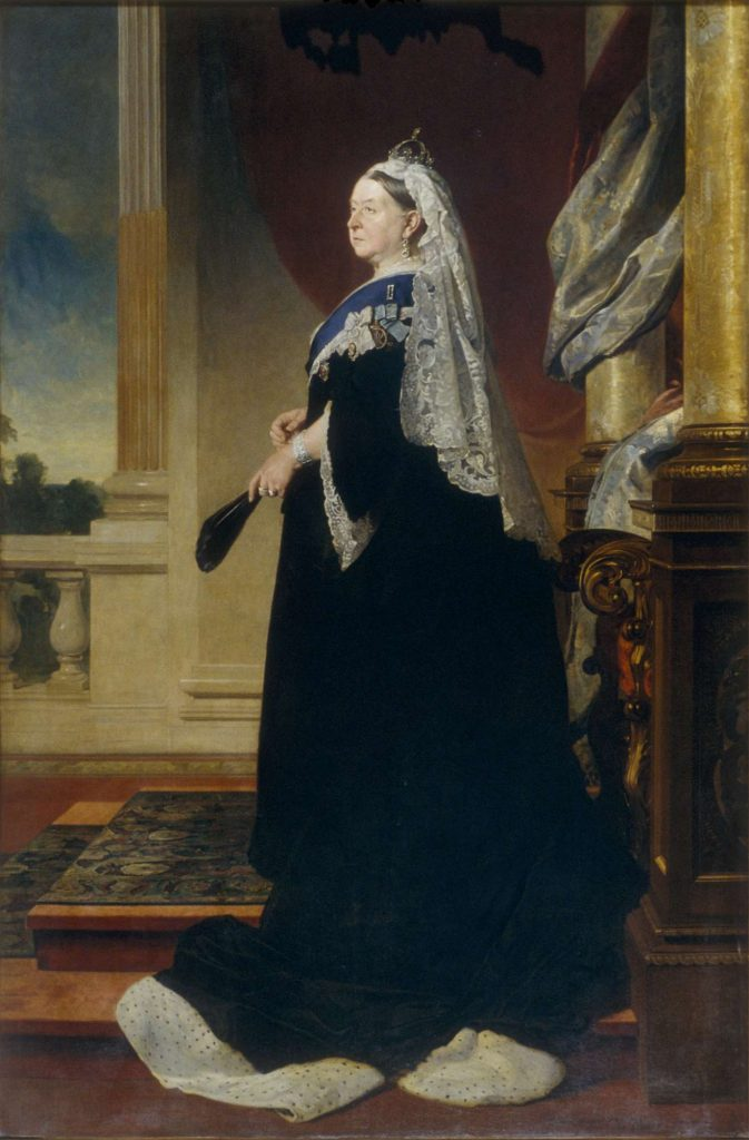 Portrait of Queen Victoria. She us wearing a crown with a white veil and is holding a fan.