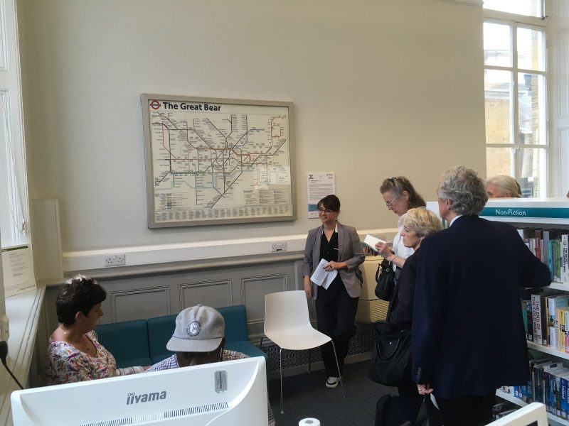 A group of people looking and talking in front of an artwork resembling the London Underground map