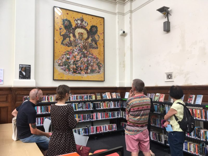 Four people looking at an artwork by Hew Locke on the wall of Walthamstow Library