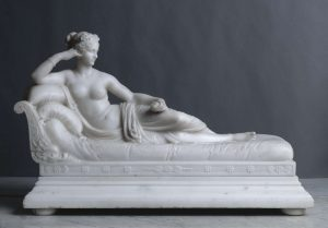 a statuette of a woman resting on a bed