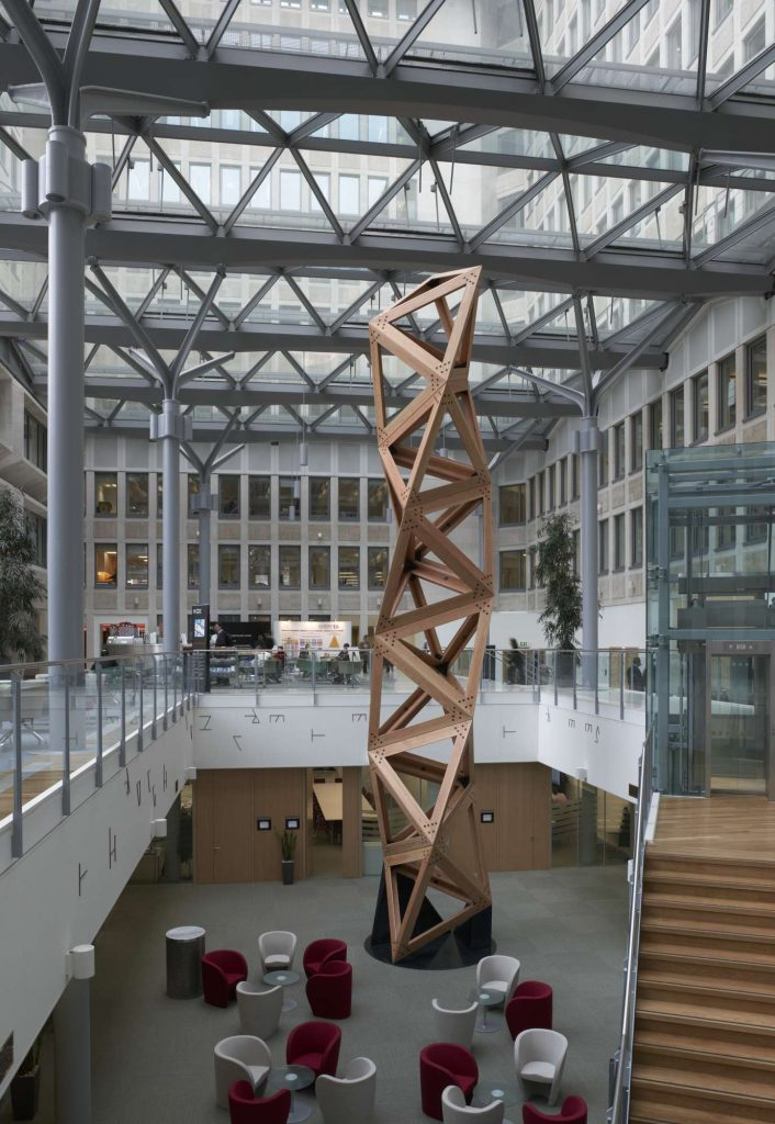 an atrium with a large sculpture made of wood