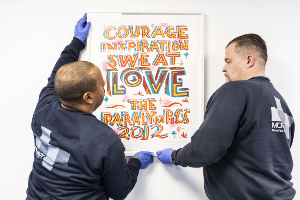 Art technicians installing a print containing the text COURAGE INSPIRATION SWEAT LOVE THE PARALYMPICS 2012