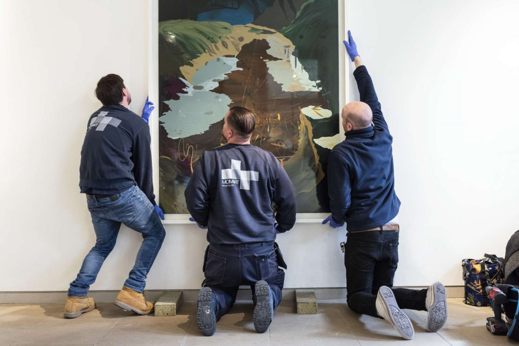 3 art technicians installing a large painting on a wall