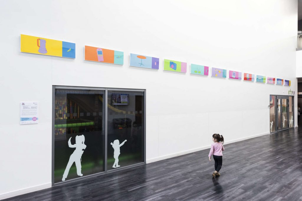 Small child walking in front of works of art