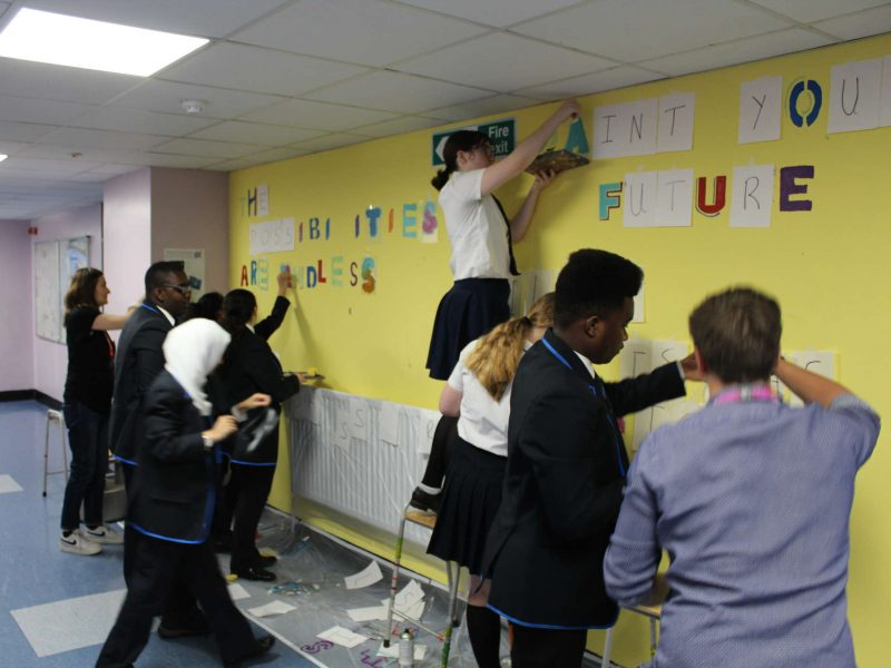 Teenagers creating a text-based mural on to a yellow wall of their school