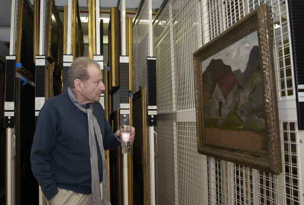 Lucian Freud visiting the Government Art Collection in 2011. He is holding a glass of water and looking at his painting in a store room.