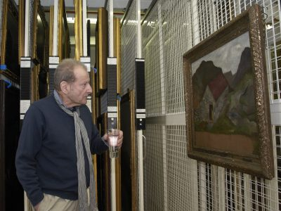 Lucien Freud visiting the Government Art Collection in 2011. He is holding a glass of water and looking at his painting in a store room.